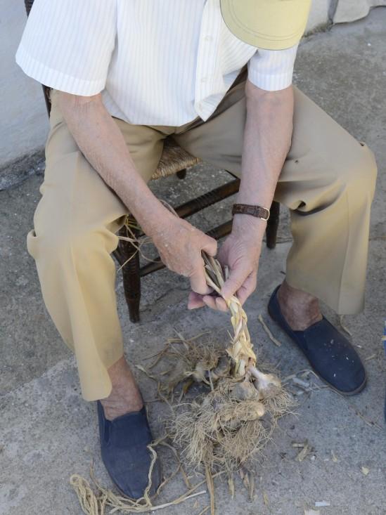 abuelo trenzando una ristra de ajos